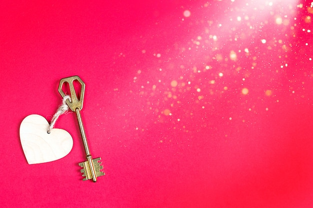 Chiave d'oro con etichetta in legno a forma di cuore su fondo rosso