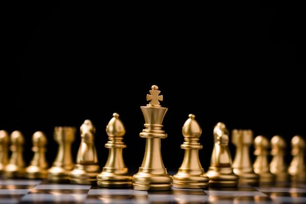Gli scacchi d'oro del re stanno di fronte ad altri pezzi degli scacchi. leadership aziendale lavoro di squadra e strategia di marketing concetto di pianificazione.