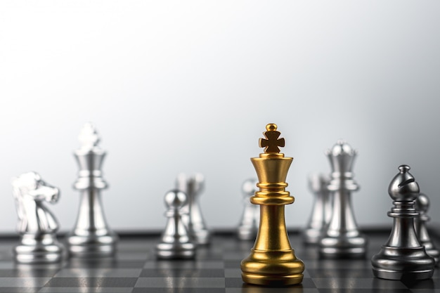 Gli scacchi del re d'oro in piedi incontrano i nemici.