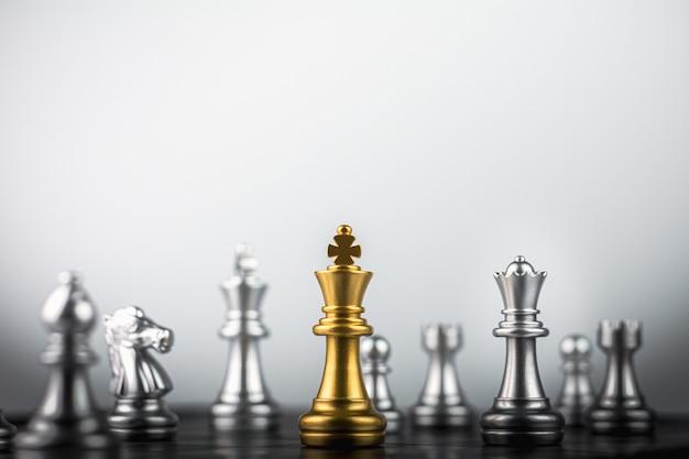 Gli scacchi del re d'oro in piedi incontrano i nemici
