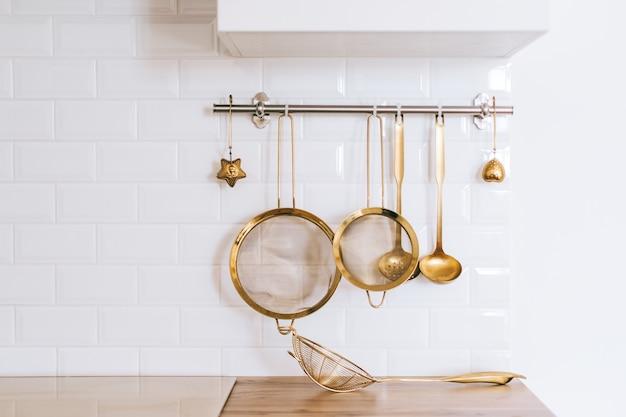 Utensili da cucina d'oro per cucinare su un muro bianco con spazio di copia.