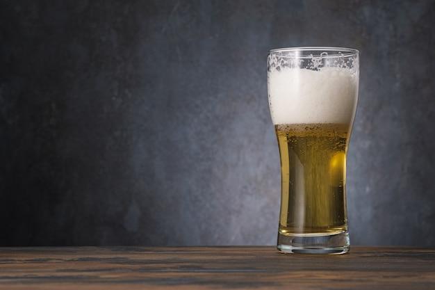 Birra chiara dorata in vetro con birra e schiuma