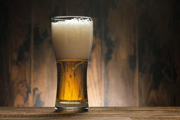 Birra chiara dorata in vetro con schiuma sulla parete di legno