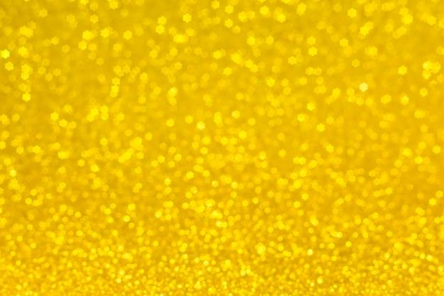 Luci dorate a forma di stelle per uno sfondo festivo. astratto, sfondo giallo brillante, bokeh sfocato.