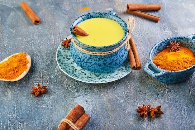Latte dorato con curcuma, bastoncini di cannella, curcuma e anice