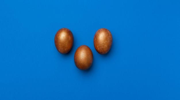 Uova di pasqua moderne dorate isolate sull'azzurro