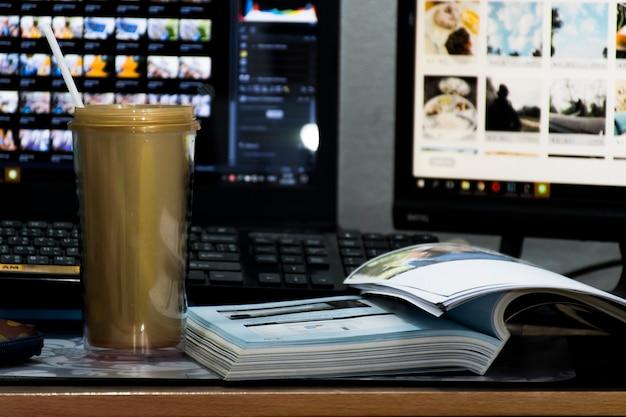 Una tazza d'oro si trova sul tavolo e un libro è posto accanto ad essa. e con lo sfondo, c'è un notebook e il monitor di un computer.