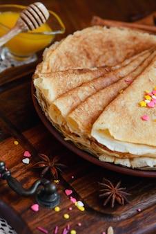 Frittelle dorate con frutta congelata, decorazioni e miele in stile rustico