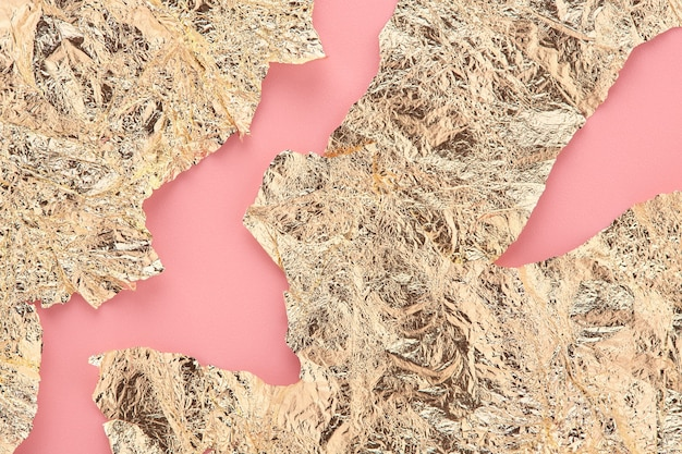 Fondo astratto di carta dorata, lamina d'oro di forma irregolare su sfondo rosa.