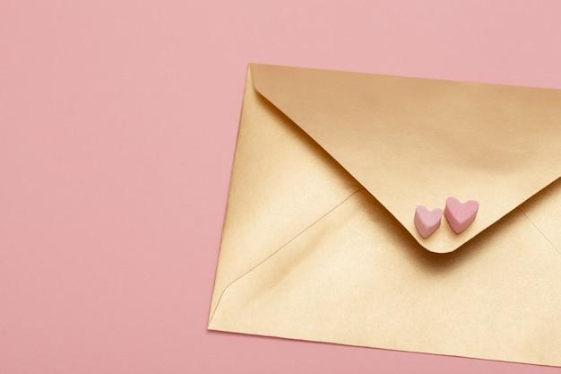 Busta di carta dorata con due cuori di marshmallow isolato su sfondo rosa