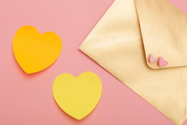 Busta di carta dorata con due cuori di marshmallow e due cuori di carta gialla isolati sul rosa