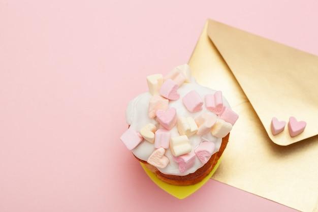 Busta di carta dorata con due cuori di marshmallow e bigné di san valentino isolato sul rosa