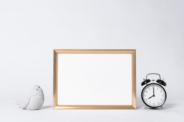 Portafoto dorato mock up e orologio elementi interni di arredamento casa.