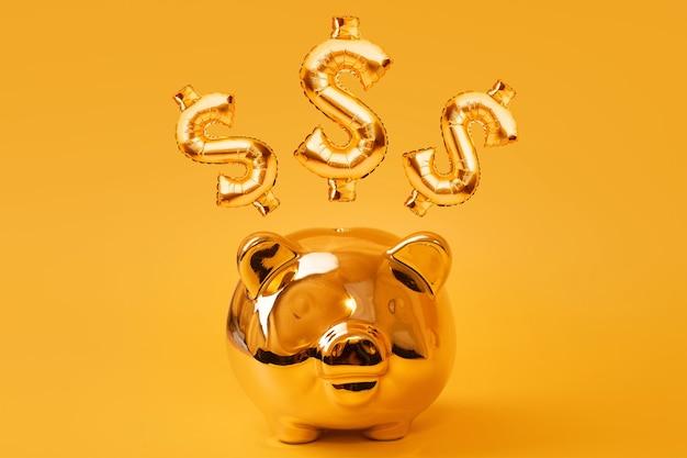 Salvadanaio dorato su sfondo giallo con palloncini segno oro usd. simbolo di valuta d'oro fatto di palloncino stagnola gonfiabile. concetto di investimento e bancario risparmio di denaro, salvadanaio, finanza, investimenti.