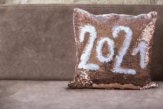 Cuscino dorato con paillettes sul divano marrone con scritta. cuscino con paillettes. posto per il testo