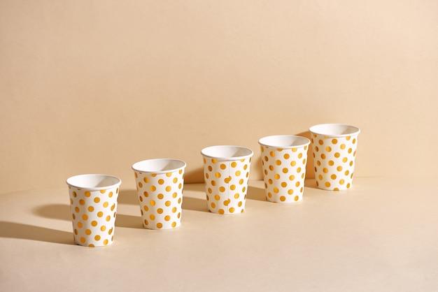 Bicchiere di carta a pois dorato isolato su sfondo beige
