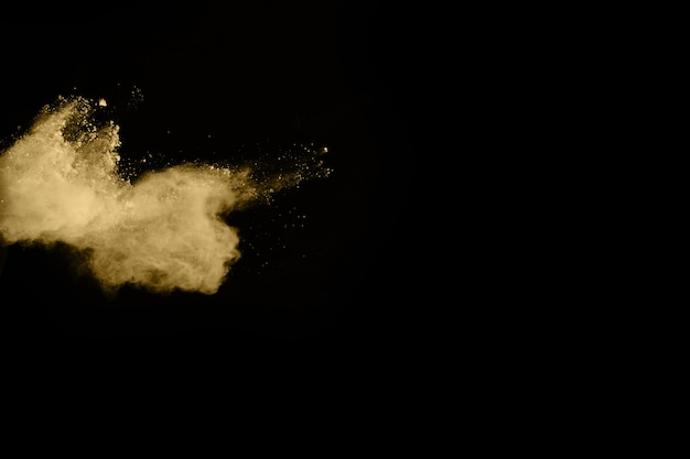 Esplosione di polvere dorata su sfondo nero. blocca il movimento.