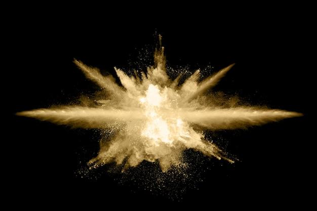 Esplosione di polvere dorata su sfondo nero.