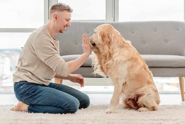 Il golden retriever dà il cinque al suo proprietario seduto sul pavimento