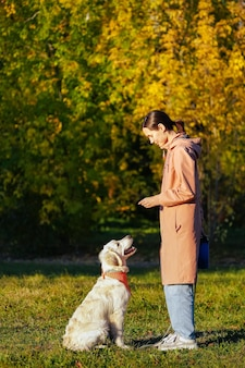 Cucciolo di golden retriever con bandana nel parco guardando la ragazza in impermeabile rosa