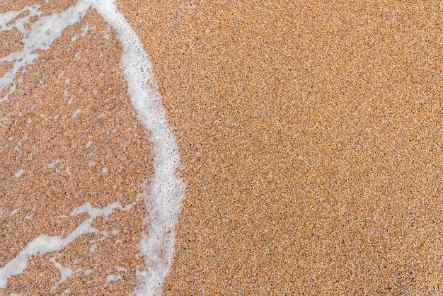 Sabbia dorata e sfondo dell'onda del mare
