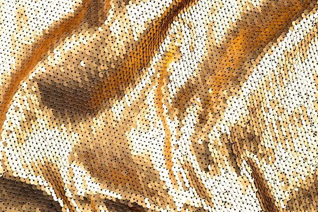 Trama del tessuto di paillettes dorate.