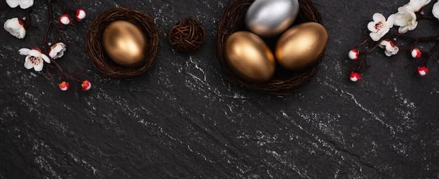 Uova di pasqua d'oro e d'argento con il fiore del fiore della prugna sul fondo nero scuro della tavola dell'ardesia.
