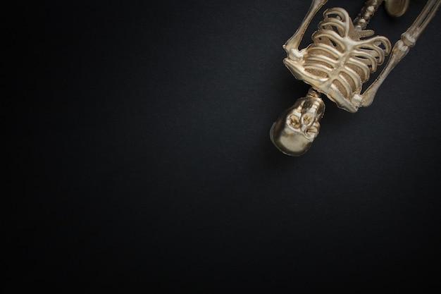 Scheletro d'oro su sfondo nero. concetto di halloween.