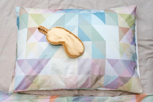 Maschera per gli occhi addormentata dorata sul letto, vista dall'alto. buonanotte, volo e concetto di viaggio. sogni d'oro, siesta, insonnia, rilassamento, stanco, concetto di viaggio non disturbare, maschera per dormire, concetto di andare a dormire
