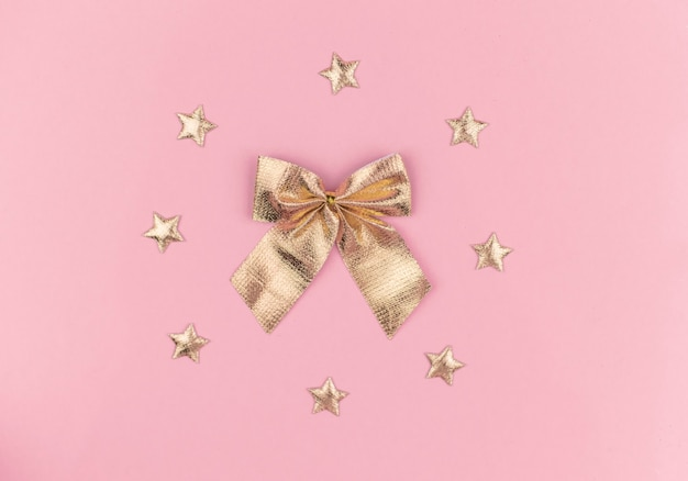 Fiocco dorato con stelle su sfondo rosa, decorazioni di capodanno, regalo 2021