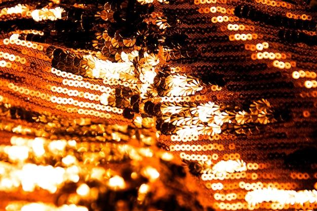 Materiale di paillettes scintillanti dorate come sfondo per le vacanze. concetto di festa. movimento sfocato.
