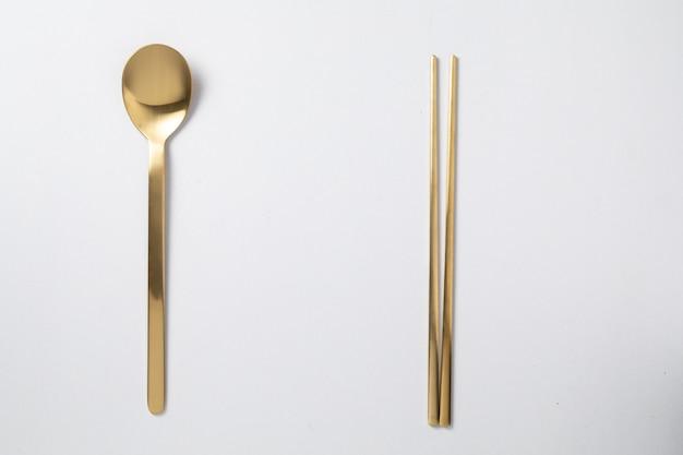Bastoncino dorato cucchiaio stile corea su sfondo bianco