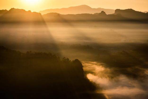 L'alba dorata risplende sulla montagna nella valle della nebbia all'alba