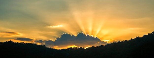 Tramonto dorato e nuvola dietro una silhouette di montagna.