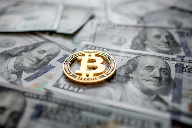 Moneta simbolica dorata bitcoin su banconote da cento dollari.