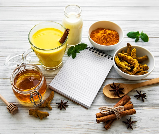 Latte dorato della curcuma in un bicchiere, spezie e ricettario su superficie di legno bianca