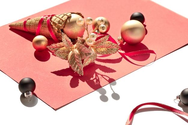 Cono gelato cialda dorata, palline natalizie oro e nere e ramoscello con bacche su carta rosa
