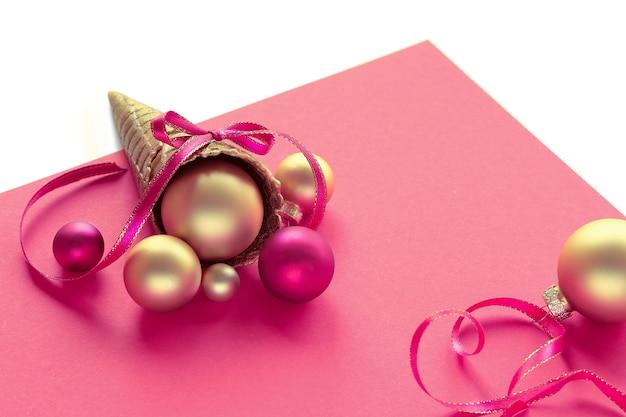 Cono gelato di cialda dorata con palline d'oro di natale, stelle e nastri su carta rosa
