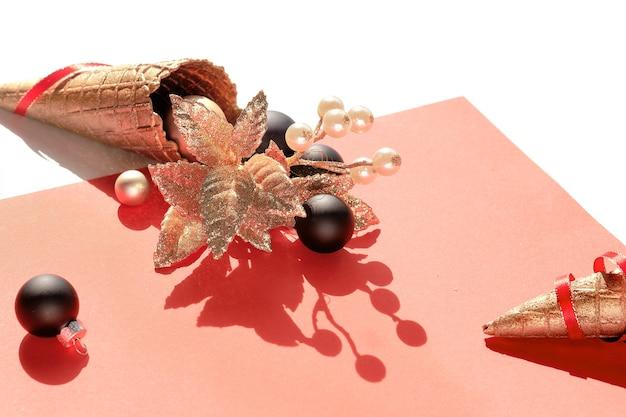 Cono gelato waffle dorato con palline natalizie oro e nere, ramoscello con bacche, stelle e nastri rossi su carta rosa