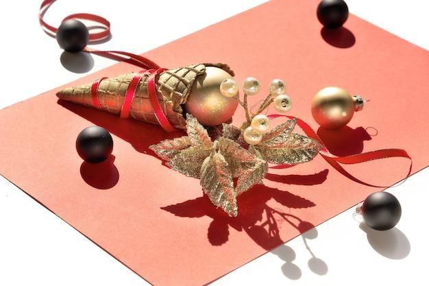 Cono gelato di cialda dorata con palline natalizie dorate e nere, bacche, stelle e nastri rossi su carta arancione