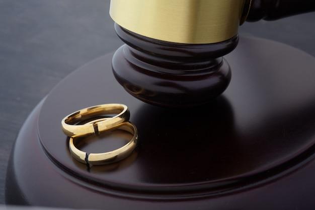 Fedi nuziali dorate con una crepa e giudice martelletto