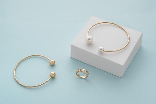 Bracciale dorato con perle su scatola bianca e bracciale e anello in oro con spazio per le copie