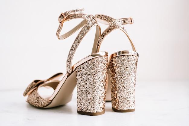 Scarpe da donna d'oro con tacchi e paillettes su sfondo bianco.
