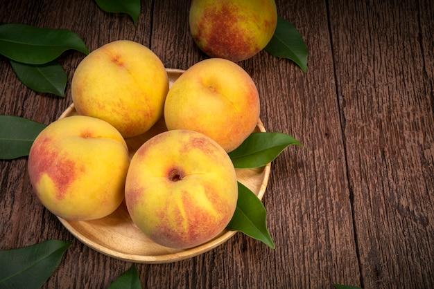 Giallo dorato in piatto di legno su tavola di legno in giardino vista dall'alto ruotare fresh honey yellow peach