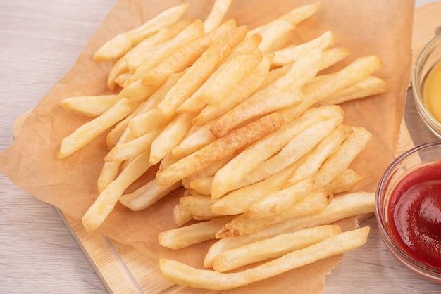 Golden gustose patatine fritte profonde su carta da forno kraft e vassoio da portata da mangiare con ketchup e senape gialla, primi piani, stile di vita.