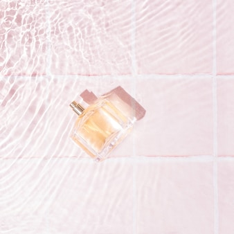 Profumo golder in acqua con piccole onde su sfondo rosa pastello con piastrelle. prodotti di bellezza femminili di lusso. stile minimale.