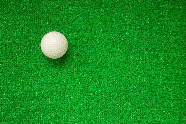 Pallina da golf su uno sfondo verde, vista dall'alto. erba decorativa verde, sfondo. pallina da golf su erba artificiale
