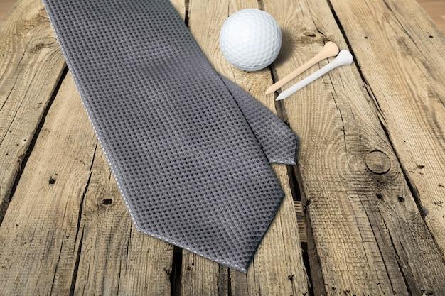 Pallina da golf, tee e cravatta sullo sfondo del tavolo
