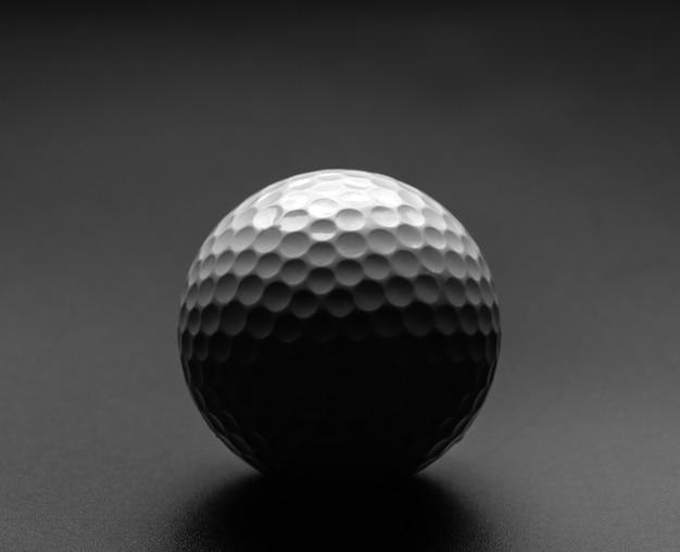 Pallina da golf con grande ombra su superficie grigia