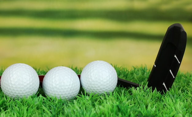 Palline da golf e driver sull'erba verde all'aperto da vicino